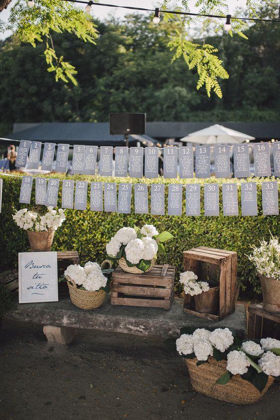 Seating plan decorado con cajas de madera y hortensias blancas en cestos de mimbre