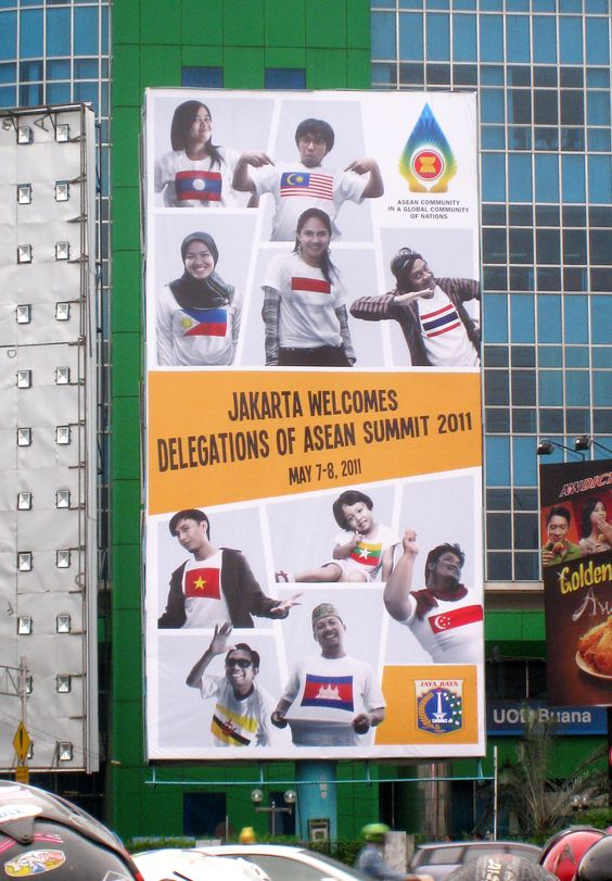 """The billboard at Harmoni intersection in Central Jakarta """"Jakarta Welcomes Delegations of ASEAN Summit 2011, May 7–8, 2011"""". Depicting Indonesians of various ages, genders, religions and ethnicities wearing T-Shirts bearing national flags of 10 ASEAN members. It should be noted that the female bearing the predominantly-Christian Philippines flag is wearing a traditional Muslim hijab to symbolize inclusiveness of ASEAN nations."""
