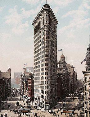 gratte ciel  Photographie d'un immeuble très effilé de forme triangulaire d'une vingtaine d'étages surplombant les bâtiments voisins et les rues en contr...
