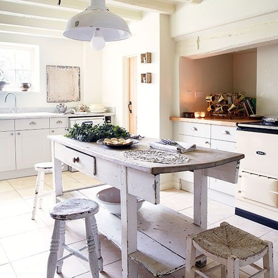 WHITE COUNTRY KITCHEN WITH ANTIQUE BUTCHER'S BLOCK - An antique butcher's block is the stunning focal point of this country kitchen and adds a rustic feel to the design.