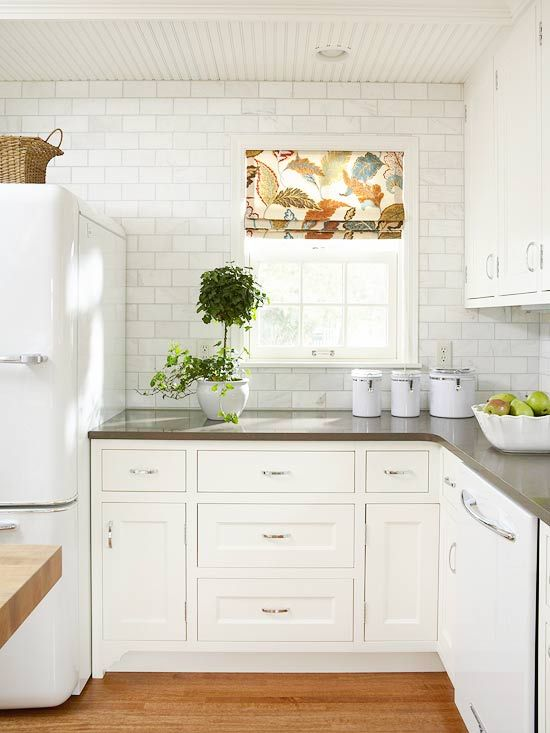 This kitchen is so bright and white!  I love the white subway tile on the walls and the rich hardwood floors. The grey counter is to die for.  I also love the vintage style fridge that ties it together.  Greenery in the kitchen is always a nice touch!