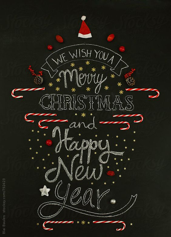 We wish you a merry Christmas and happy new year, written on a chalkboard and composed with Christmas ornaments.: