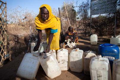 Internally Displaced Persons (IDPs) at the Nifasha Camp in North Darfur, have access to water only two hours in the morning, not enough time for all to be fully provided. A woman leaves a water access point with empty jerry cans just after the enforced closing time. 15 January 2014 Shangil Tobaya, Sudan. Photo # 577172. UN Photo/Albert González Farran