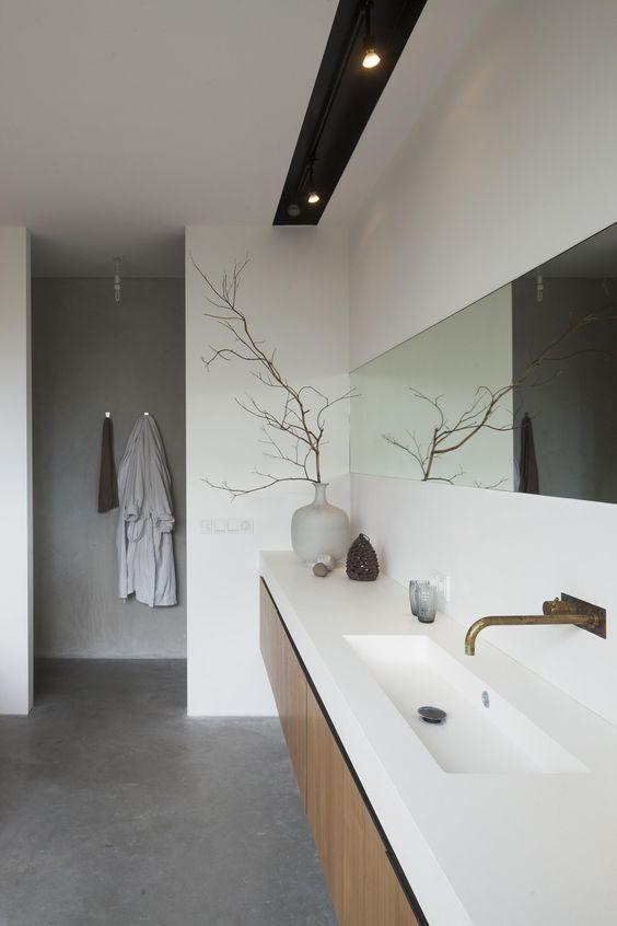 Rustige zen-badkamer met mooie gietvloer. Een spiegel over de hele breedte van de muur geeft een extra ruimtelijk effect.