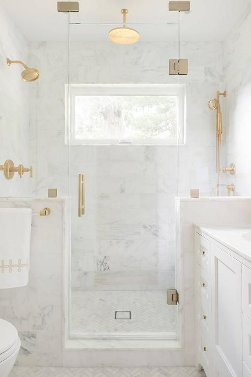A brass and lucite towel holder lines a glass and marble shower enclosure filled with white marble tiles lined with a brushed brass shower kit alongside a white marble herringbone tile shower floor.: