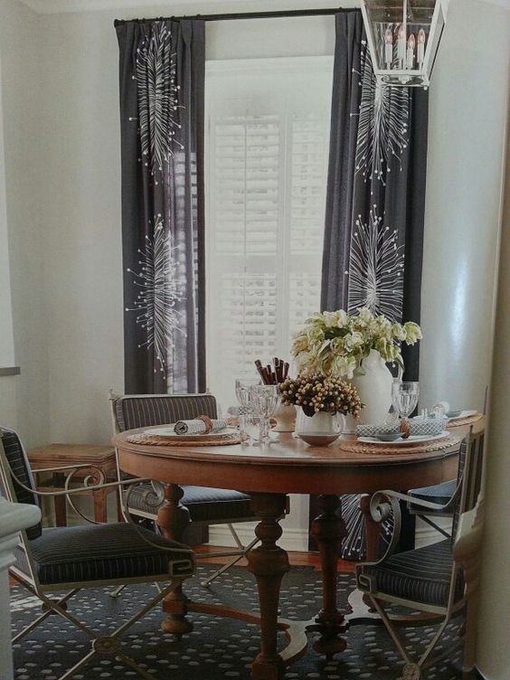 whimsical curtains in organic oversized print, pinstriped chairs, anchoring warmth of antique wood table set with texural neutral elements