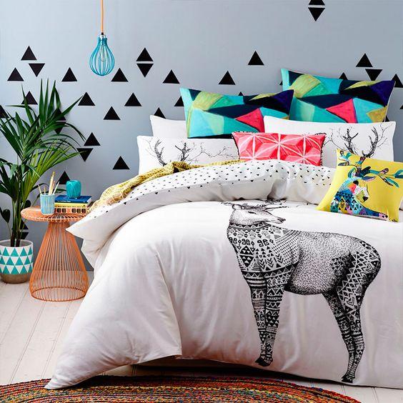 Grafismos na cabeceira com triângulos de adesivo vinílico: