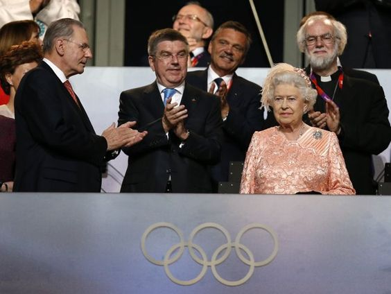The President of the International Olympic Committee Jacques Rogge, left, and Britain's Archbishop of Canterbury Rowan Williams, back right, applaud as Britain's Queen Elizabeth II, foreground right, arrives during the Opening Ceremony at the 2012 Summer Olympics, Friday, July 27, 2012, in London.