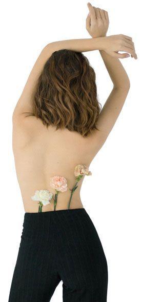 chica de espaldas sin blusa con 3 claveles que salen del pantalón, brazos en alto