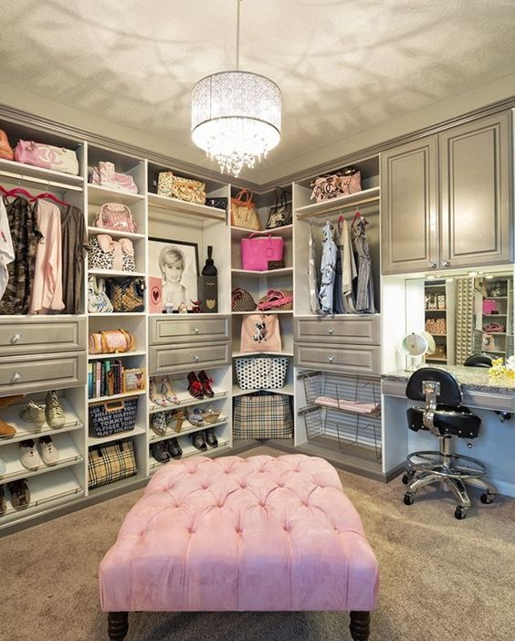 Walk in closet with grey tone shelves and cabinets and pink chair #glass #cabinets #closet #storage #organization #allenrothCloset #allenAndRothCloset #closetShelves