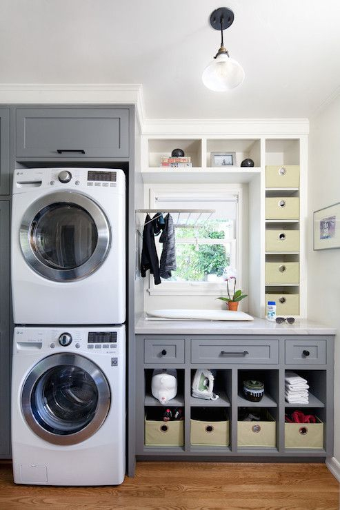 Family friendly laundry room boasts stacked washer and dryer framed by gray cabinets beside laundry folding counter featuring upper and lower storage cubbies and a fold down drying rack in front of window