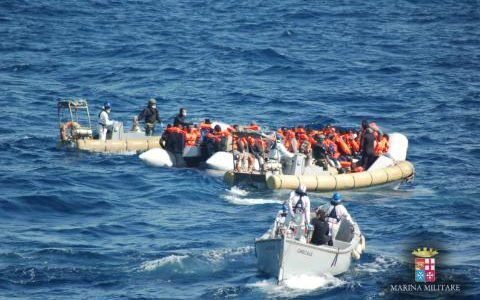 In this photo taken on Wednesday, March 16, 2016 migrants on a dinghy boat are rescued by Italian Navy's personnel off the coast of Lampedusa island, Italy.