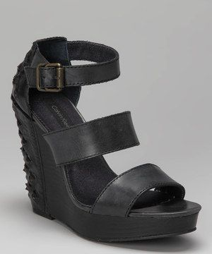 Elegant in front and edgy in the back, these chic studded leather wedges flaunt wide, flexible straps with a soft denim lining and adjustable buckle, so sporting rockstar-worthy steps is as comfy as it is classy.