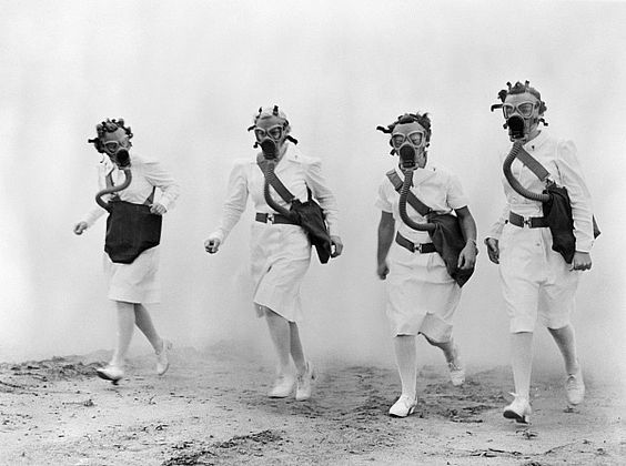U.S. Army nurses advance through a cloud of smoke in a gas mask drill during training at Scott Field, Illinois. Photograph, c1942.