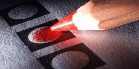 Een stembiljet dat word ingekleurd met een rood potlood. Maud: