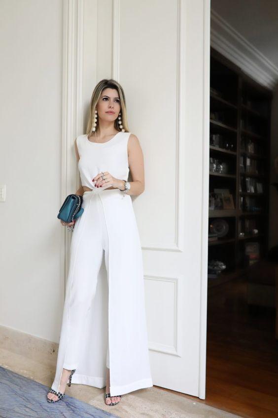 Carol Tognon usando um macacão branco, bolsa azul, brinco de bolas e sandália preta com listras brancas.: