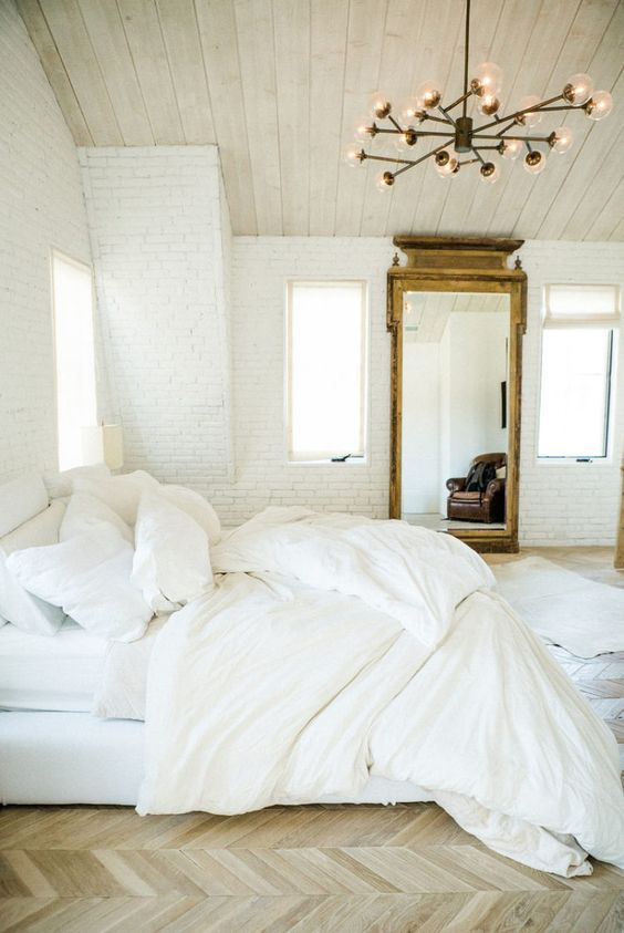 A Leanne Ford designed bedroom with black Sputnik chandelier, herringbone wood floors, white linen bedding, white brick walls, wood ceiling in a cool chic vintage style by #LeanneFord.