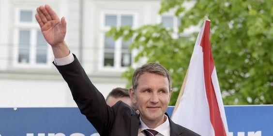 Mann hebt den rechten Arm vor einer weiß-roten Fahne