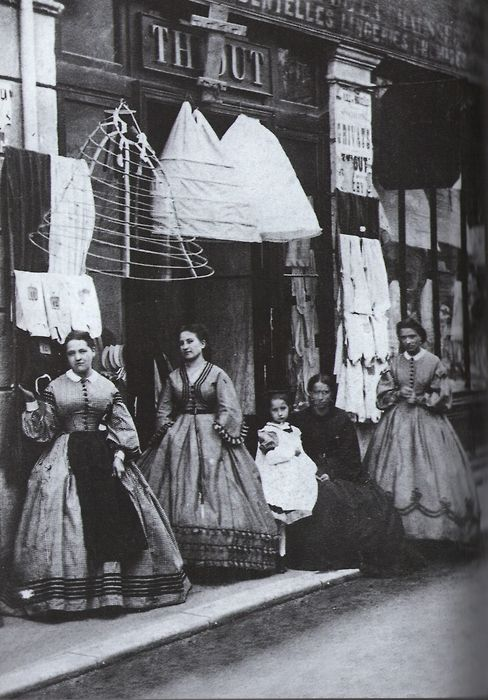 "Ca.1860, and NOT by Eugene Atget. This has been passed around labelled ""The Crinoline Shop, by Eugéne Atge, 1880,"" but that is obviously wrong. Eugéne Atget (note the final T) was born in 1857 and did not start taking photographs until the late 1880s, nor his famous street scenes until the end of the century. This image is clearly between 1860 and 1864 by the fashions - but it does appear to be French.:"
