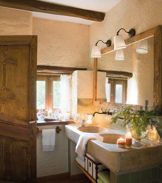 El espejo del baño se diseñó con vigas de la cubierta, al igual que algunas ventanas. Pila de piedra de Rajoleria Llensa. Espejo realizado por Isaias Lumbreras con madera recuperada. Toallas de Zara Home.