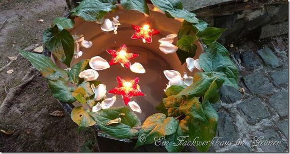 Leuchtkerzen in einem kleinen Teich machen die  Abende im Garten erst so richtig gemütlich.