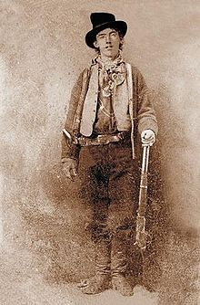 """William H. Bonney (born William Henry McCarty, Jr), better known as Billy the Kid, was a 19th-century American gunman who participated in the Lincoln County War and became a frontier outlaw in the American Old West. Contemporaries described him as a """"neat"""" dresser who favored an """"unadorned Mexican sombrero"""".  These qualities, along with his cunning and celebrated skill with firearms, contributed to his paradoxical image as both a notorious outlaw and beloved folk hero."""