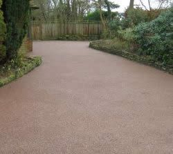 Resin-bonded gravel Aesthetically pleasing and easy to maintain. Solves the problem of sloping drives. During dry weather, there isn't the issue that's commonly found with gravel driveways of dust being kicked up by cars. A cheaper (if less elegant) finish would be to mix the gravel with some tar to hold it in place. Different colors available for both the resin and the aggregate materials.