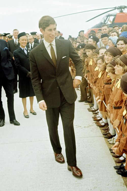 A rare single-breasted suit shot: chocolate brown wool birdseye with slim lapels, tapered trousers. With white shirt, chestnut brown cap-toe oxfords, slim mustard tie: Prince Charles, circa late 1960s.
