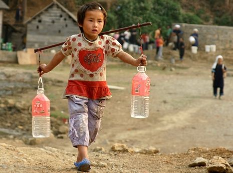 A girl carries bottles of water fetched from a mountain spring in China's Guizhou province