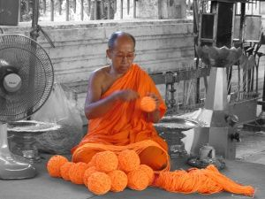A monk wraps yarn into balls