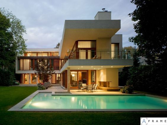 The Ravine Residence by Hariri Pontarini Architects. I like this photograph as much if not more than the actual house. I like how the photo was taken at a time of day where the sky's brightness matches the lights of the residence so that they appear to glow. It gives the whole image a soft, warm look. Regarding the house, I love all the windows, the natural wood, the layout and shape of the house, the flat looking pool and how it is bordered by stone and then lawn.