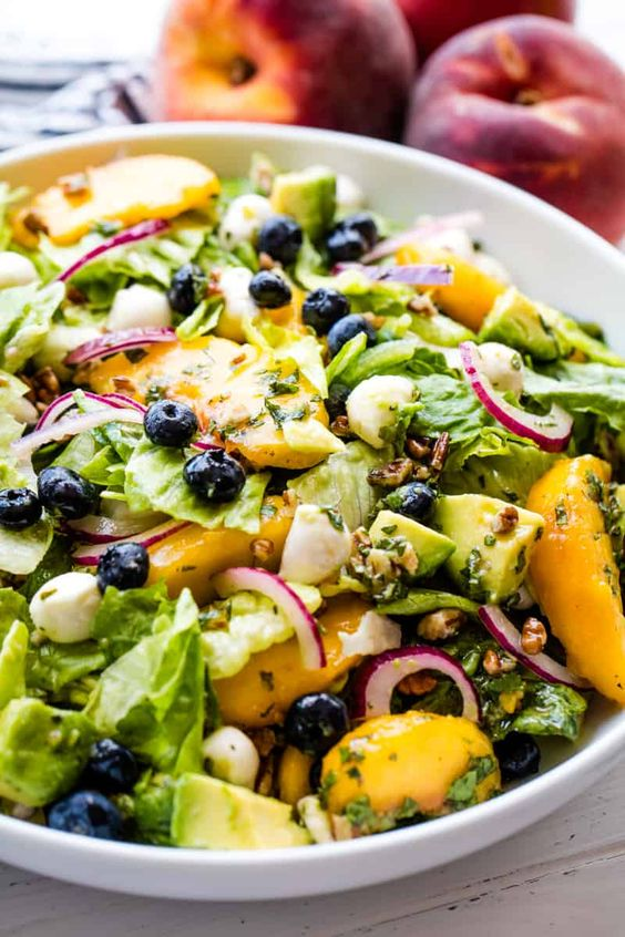 Meet your new favorite salad! Summer Peach Salad is full of the sweet flavors of late summer with peach, blueberry, avocado, mint, mozzarella and more! #thestayathomechef #summerpeachsalad #summersalad #saladrecipe #peach
