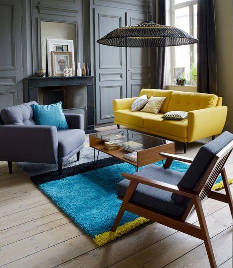 Un canapé jaune et un tapis bleu vif réveillent le salon gris