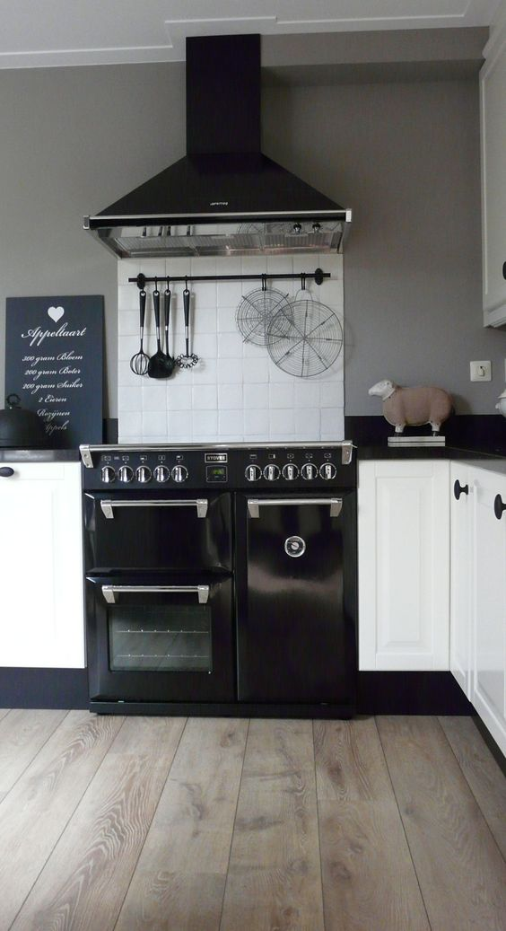 black appliances, white cupboards with black handles, washed wide plank flooring.