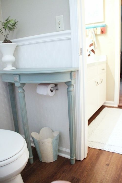 Add a half table over a toilet paper holder to save space in a small bathroom.
