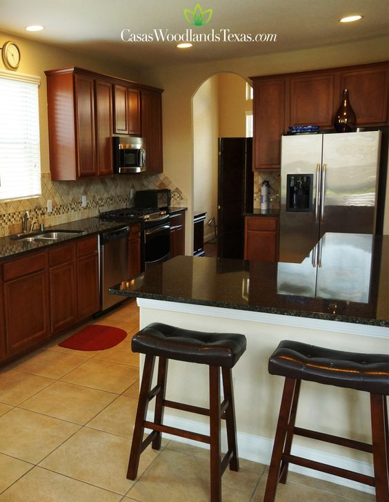 Amplia cocina con gabinetes de madera y piso de azulejo for Decoracion de gabinetes de cocina