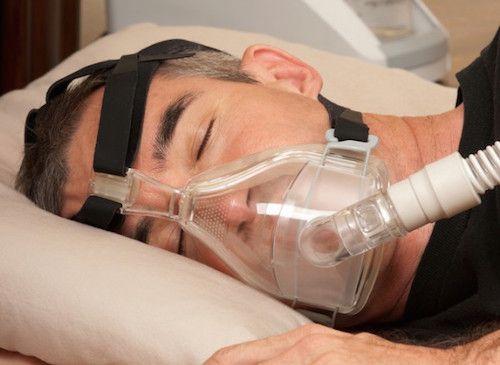 Homme qui dort avec un appareil pour lutter contre l'apnée du sommeil.
