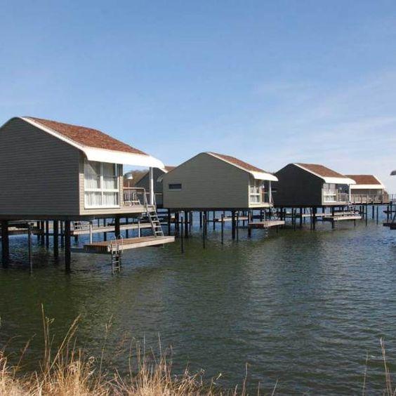 Pfahlhäuser in der Sonne mit Bootssteg.