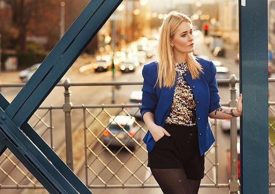 Christina Key is wearing a striking blue jacket and a black hot pants