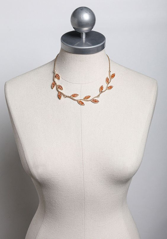 This gold-toned necklace features a textured branch-inspired design accented with beaded leaves in a peach hue.
