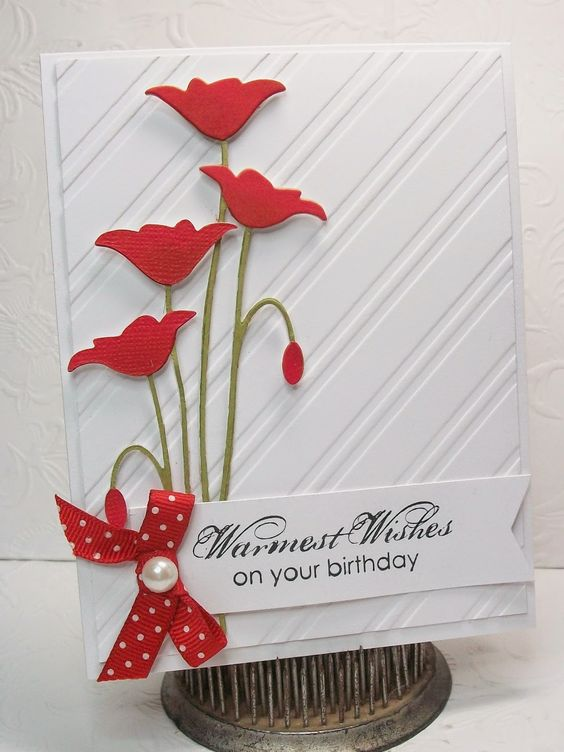 """By Vicki. Die cut """"Prim Poppies"""" (Memory Box) from white. Ink flowers with Real Red and stems with Old Olive. Sponge base of each flower with Cherry Cobbler. On white card base, add dry embossed white panel (""""Stripes"""" embossing folder). Pop up poppies onto card. Add sentiment, bow, pearl."""
