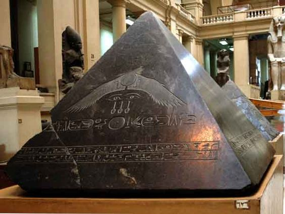 Pyramidion (top of a pyramid) dedicated by Amenemhet III , ruled 1831-1986 BC. The winged sun disk depicted in the center of the stone,  carving art on the black granite is amazing.    Found among debri on the eastern side of the pyramid in 1900 the capstone of the pyramid was carved from a block of black granite. A pair of eyes similar to those on the eastern side if his sarcophagus, together with some other hieroglyphic components are inscribed on the eastern side of the capstone.