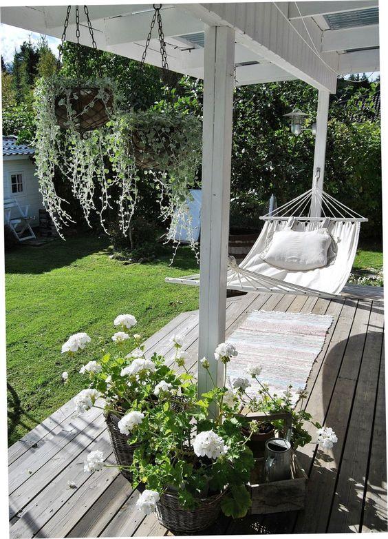 Wit gecombineerd met hout zorgt voor rust in de tuin. Ik zou het heerlijk vonden om even te dutten in mijn hangmat op de veranda.: