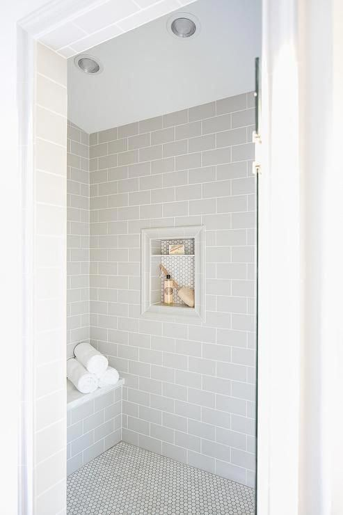 A Glass Door Opens To A Walk In Shower Clad In Light Gray Subway Wall Tiles Fixed Surrounding A Tile In 2020 Shower Tile White Subway Tile Bathroom Shower Tile Designs