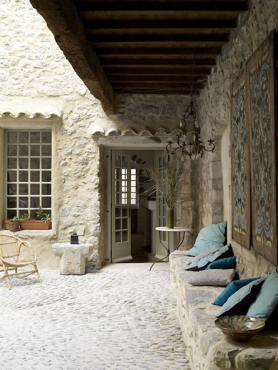 suelo de piedra (cantos rodados grandes) distinta a los muros pero en combinación, con una línea que delimita y hace una geometría. Murete de piedra para asiento