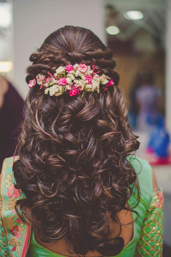 Beautiful hairdo | twisted braids adorned with flowers is adding freshness to the rest of the curled locks | Function Mania | Hairstyles for Indian Bridesmaids | 7 Easy Hairstyles for Bridesmaids Trending this Season!