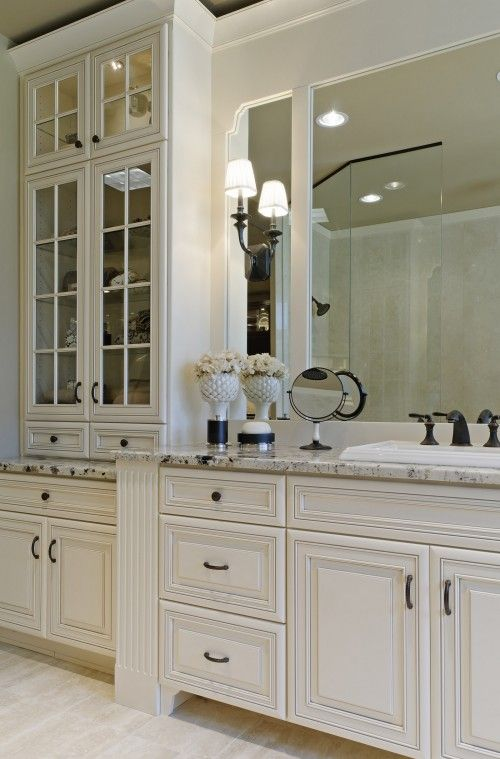 Lighted glass cabinetry. Mirror detail (look at the pretty corner!) Sconce on mirror. Marble. White.