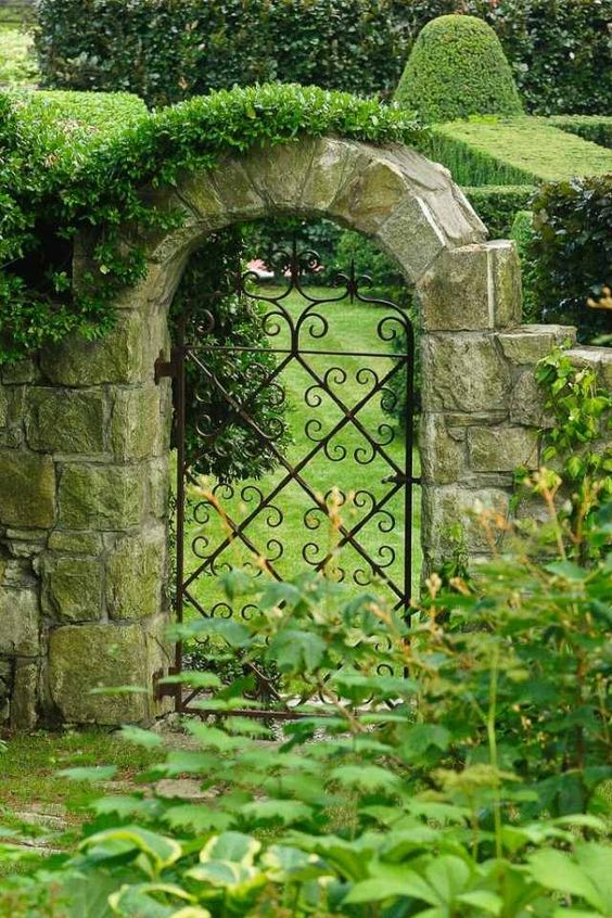 Garden gate ideas and inspiration: An arched iron gate framed by stone leads to lush green garden. #gardenideas #gardengate #irongate