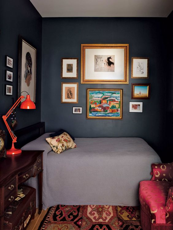 Inside the jewel-box bedroom, dark walls in Benjamin Moore's Blue Note highlight the art.  The steel bed is from Room & Board. The Georgian Revival desk is from the 1920s; the hand-carved chest beneath is from Honduras, where Urbano was posted with the Peace Corps.  Photo: Annie Schlechter