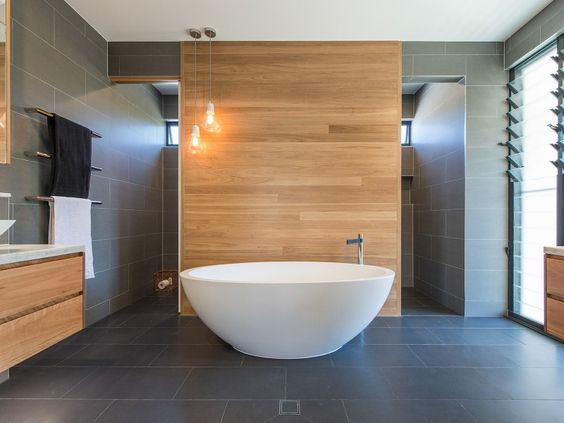 Love this look in the bathroom - timber wall tiles with dark grey floor tiles and white free standing bath